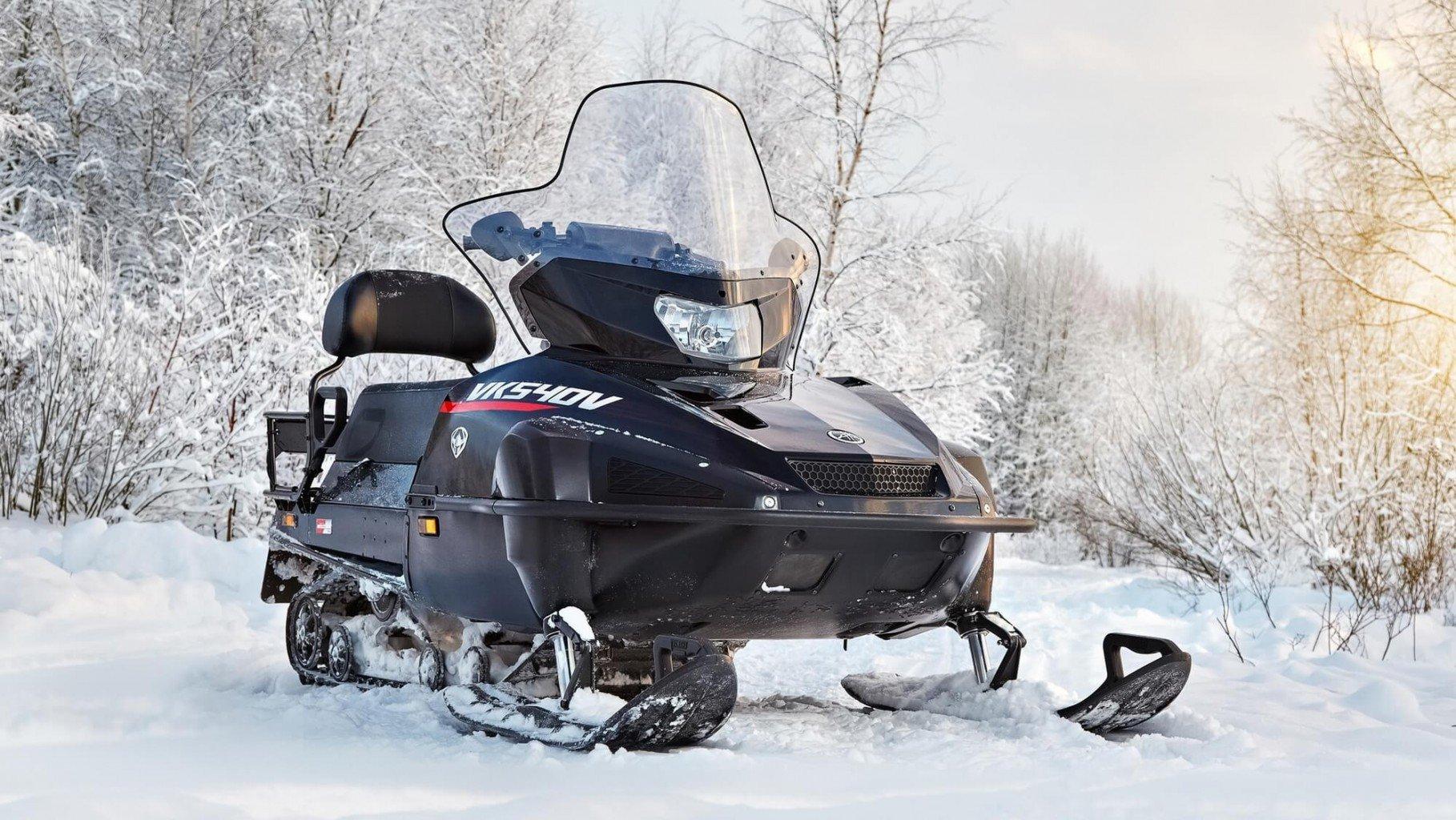 На фото новый снегоход Викинг 540 5-го поколения на фоне заснеженного леса (Viking VK540V)